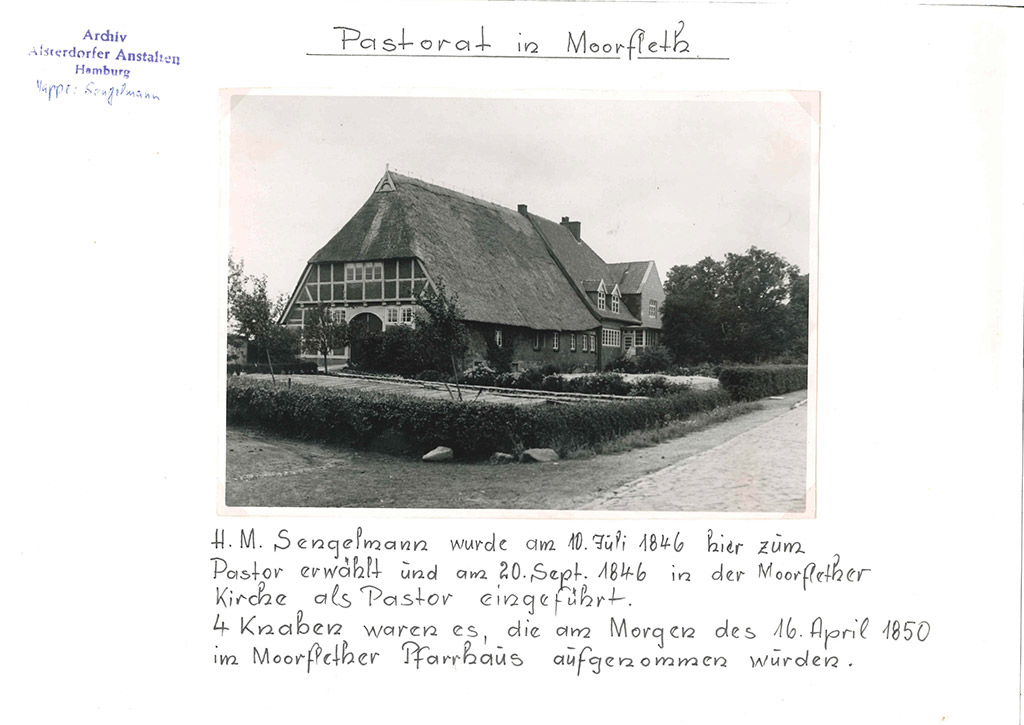 Das Foto zeigt ein großes, reetgedecktes Haus. Im Vordergrund ist ein Garten zu sehen, wo kleine Bäume stehen. Rechts, im Hintergrund des Bildes steht ein deutlich größerer Baum. Um das Haus herum wurde eine niedrige Hecke gepflanzt.
