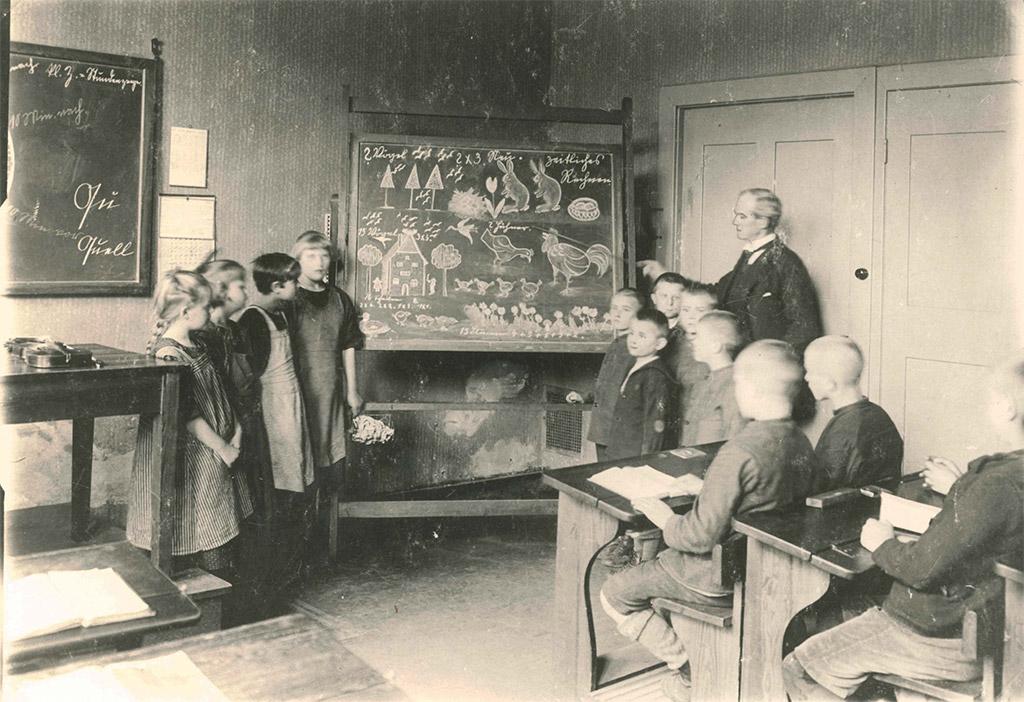 Klassenzimmer; Blick auf eine Tafel mit verschiedenen Zeichnungen. Drum herum stehen Schulkinder, hinter ihnen der Lehrer. Er zeigt mit einem Stock auf die Tafel, die anderen Kinder auf den Schulbänken im Vordergrund des Fotos schauen nach vorne. Links sieht man das Lehrerpult, dahinter hängt eine Tafel an der Wand.