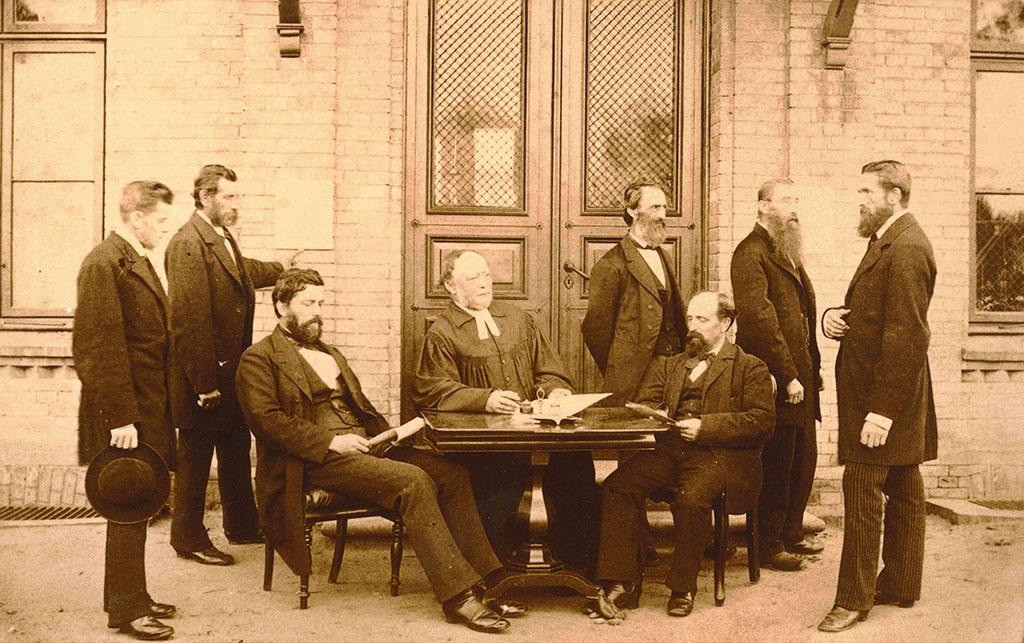 Pastor Sengelmann sitzt mit zwei Männern an einem kleinen, dunklen Tisch. Rechts und links daneben stehen fünf Männer, die Anzüge tragen. Der Mann vorne links im Bild hält einen Hut in seiner Hand. Im Hintergrund ist eine riesige Eingangstür zu sehen.