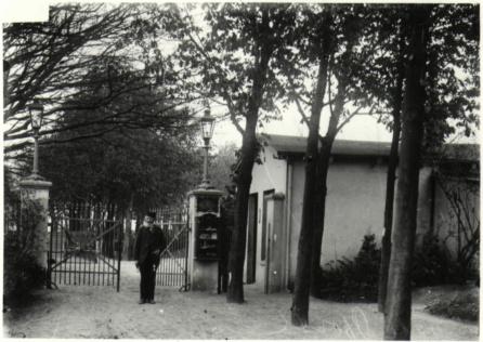 Auf der rechten Seite stehen mehrere Bäume, dahinter ist eine Hauswand zu sehen. Links führt eine Auffahrt hin zu einem halb-geöffneten Tor, vor dem ein Mann mit dunkler Kleidung und Hut steht. Auf den Torpfosten stehen Laternen, am rechten Pfosten hängt ein großer Briefkasten.