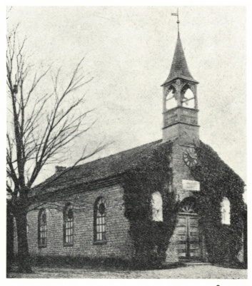 Zu sehen ist eine alte Kapelle, die schräg von vorne fotografiert wurde. Links im Bild sieht man einen kahlen Baum. Die Vorderseite der Kapelle ist mit Efeu bewachsen. Vorne auf dem Dach der Kapelle, hier rechts zu sehen, sitzt der Glockenturm.