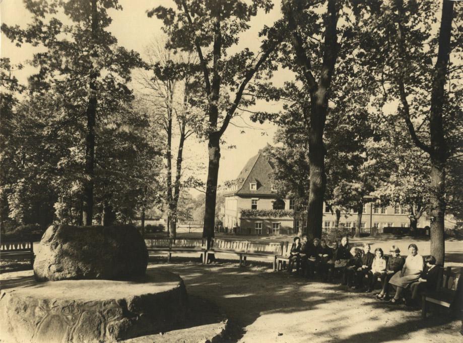 Vorne links der große Gedenkstein, rundherum bilden Bäume einen Halbkreis. Vorne rechts sitzen auf einer Bank zahlreiche Kinder, die in die Kamera schauen. Im Hintergrund steht ein großes Haus, das von den Blättern der Bäume halb verdeckt wird.