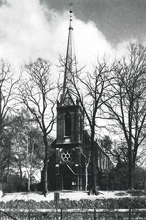 Im Vordergrund stehen blätterlose Bäume nebeneinander. Dahinter befindet sich die Kirche St. Nicolaus, man blickt auf den Eingang und den Kirchturm. Das lange Fenster im Turm gibt Sicht auf die Glocke, darüber die Kirchenuhr. Das Dach des Turms ist nach oben hin spitz-zulaufend.